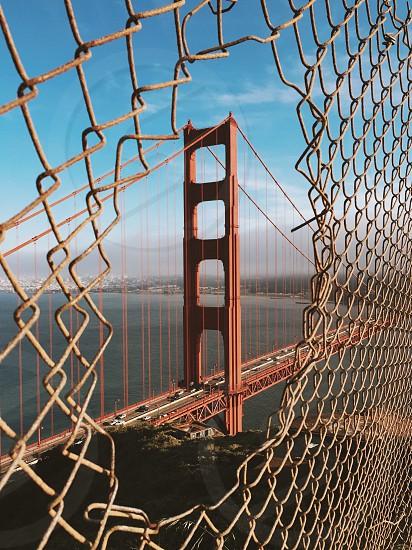 golden gate bridge view through a hole on galvanized fence at daytime photo