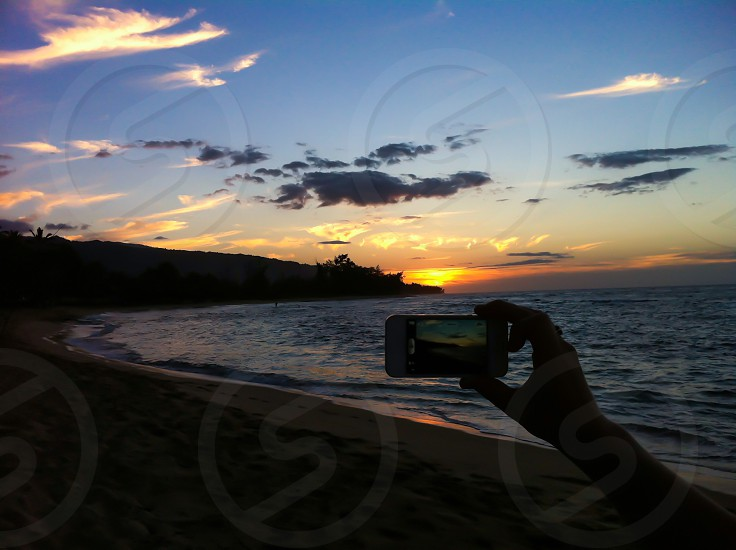 A mobile photographer captures the beauty of a Hawaiian sunset.  photo