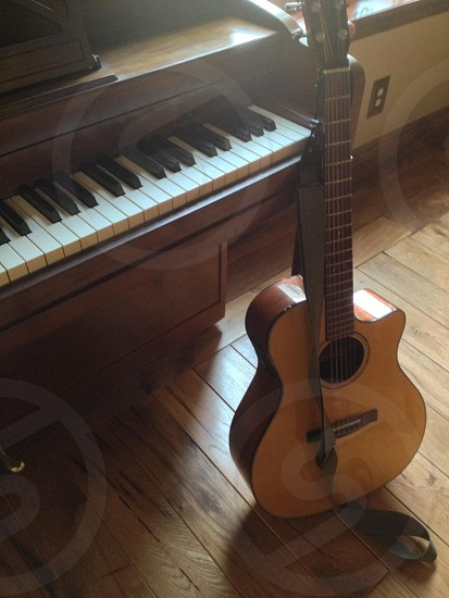 brown wooden acoustic guitar on brown wooden piano  photo