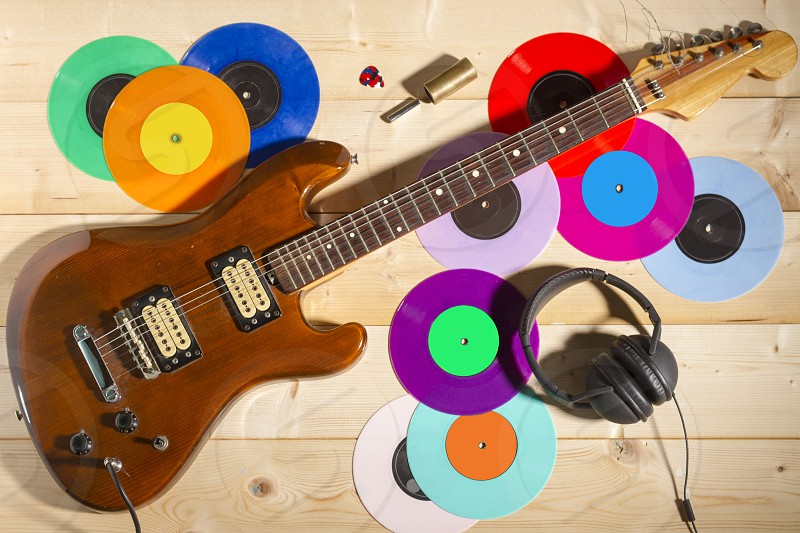 Electric guitar and vinyl records on wooden background photo