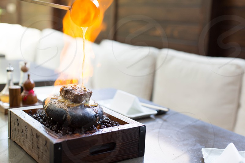 burning alcohol poured from a ladle to brown tray photo