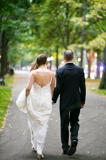 man wearing black suit and woman wearing white gown photo