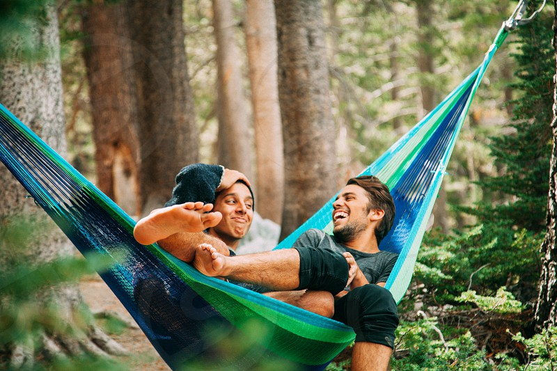 2 men in green and blue hammock under tree at daytime photo