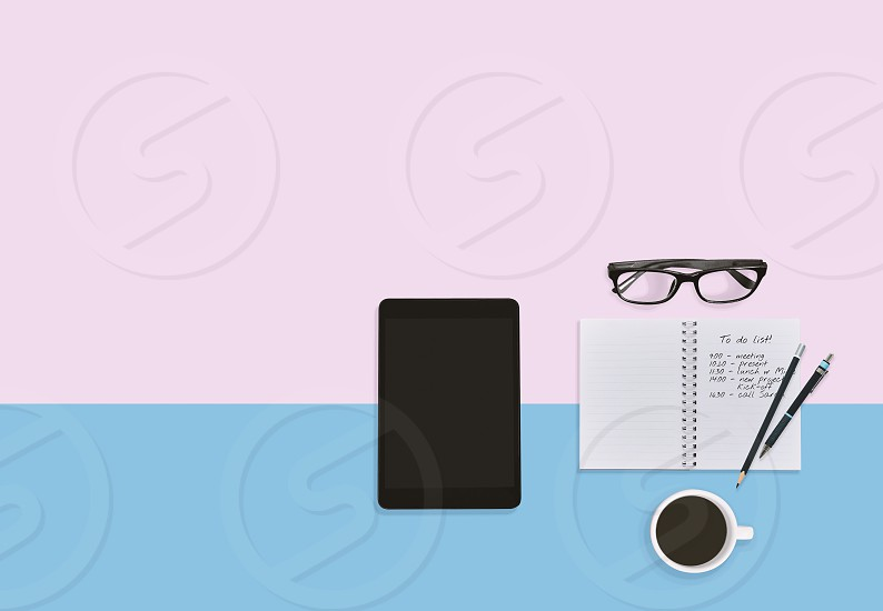 Personal business man working space desktop in pastel color background with notes in notebook eyeglasses tablet pen pencils and coffee cup with copy space. Business plan working space concept. photo