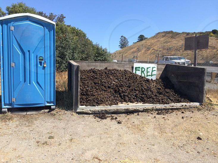 brown soil beside blue portable bathroom during daytime photo