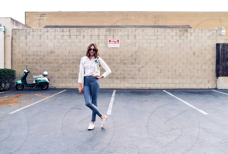 woman wearing white buttoned down shirt and blue pants on parking space photo