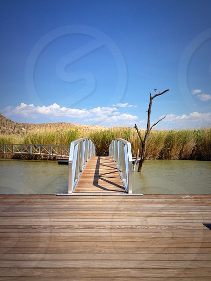 view of brown paneled bridge with white railing photo