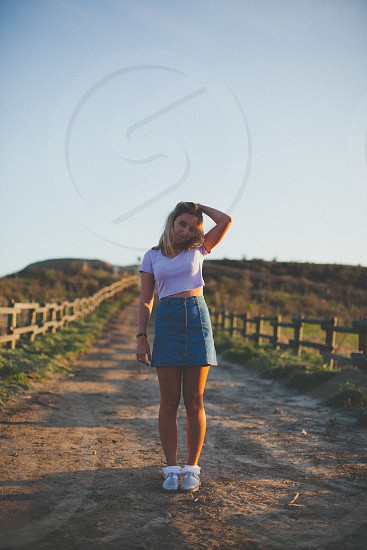 blonde girl in pink crop top and blue denim skirt standing on dirt trail lined with wooden fences photo