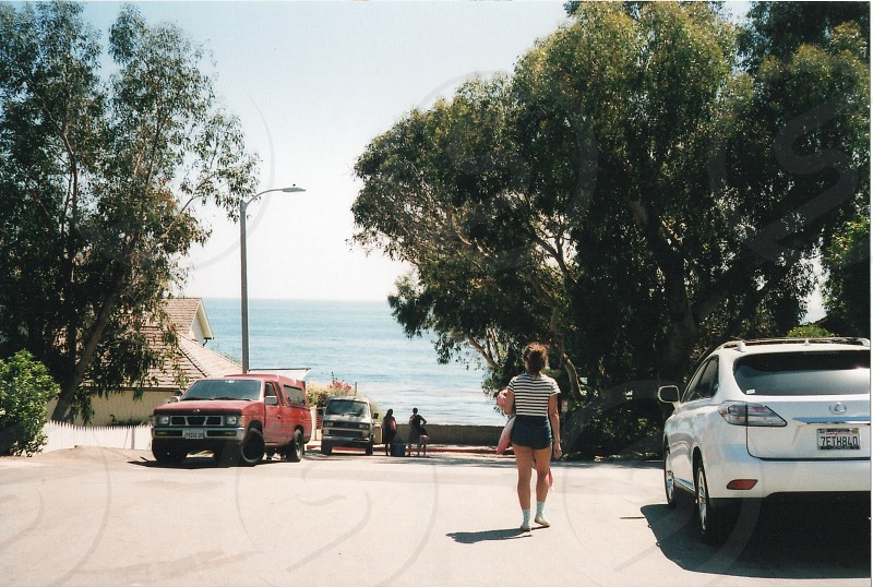 woman in black and white striped short sleeve shirt and black shorts walking past white lexus suv down hill towards blue ocean photo