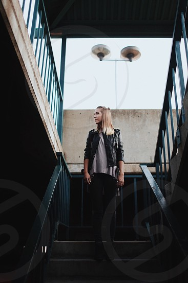 women's black leather jacket and gray shirt with black pants standing on balustrade photo