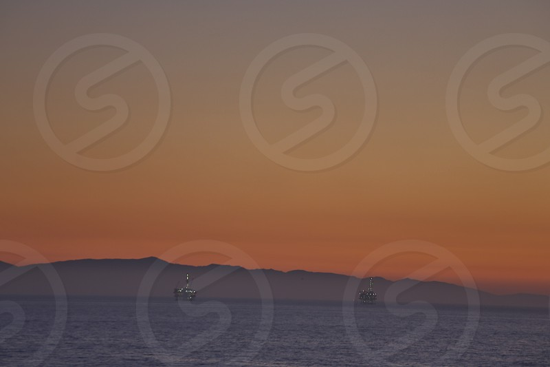 Oil rigs in the ocean during sunset photo