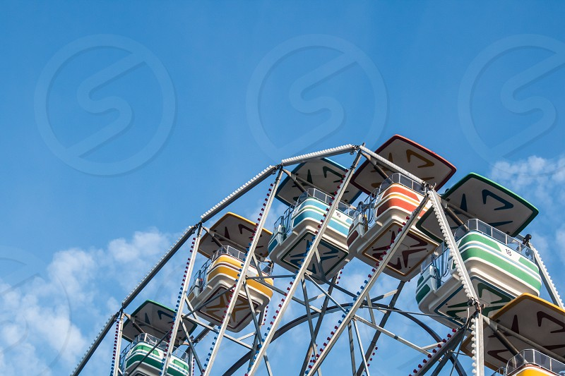 The upper portion of cars on a ferris wheel with a background of blue sky and clouds. photo