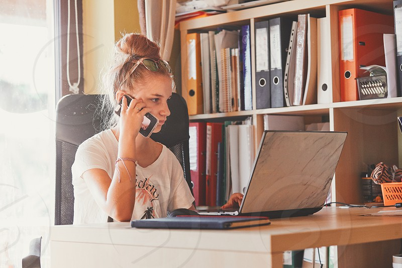 Young woman working at home using portable computer sitting at desk in home office. Candid people real moments authentic situations photo
