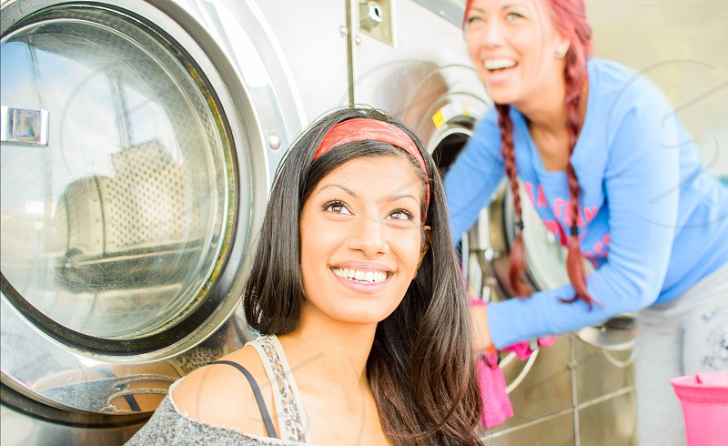 Brown Haired Girl Sitting in Front of Front Loading Washing Machine photo