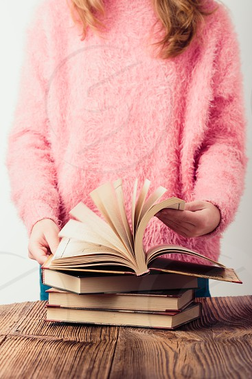 Young girl turning the pages of book in library A few books on a wooden table. Teenager girl wearing pink sweater and blue jeans. Vertical photo photo