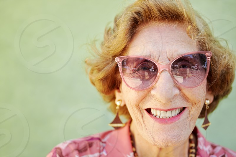 senior; old; happy; smiling; health; eyewear; woman; 60s; 70s; aged; camera; caucasian; cheerful; confidence; confident; copy space; delighted; elderly; enjoy; eyeglasses; female; fashion; fun; funny; glad; good news; grandmother; green; hair; happiness; head and shoulders; healthy; lifestyle; looking; looking at camera; natural; one; one person; optimistic; outdoors; people; person; pink; portrait; proud; retired; retirement; satisfaction; wall photo