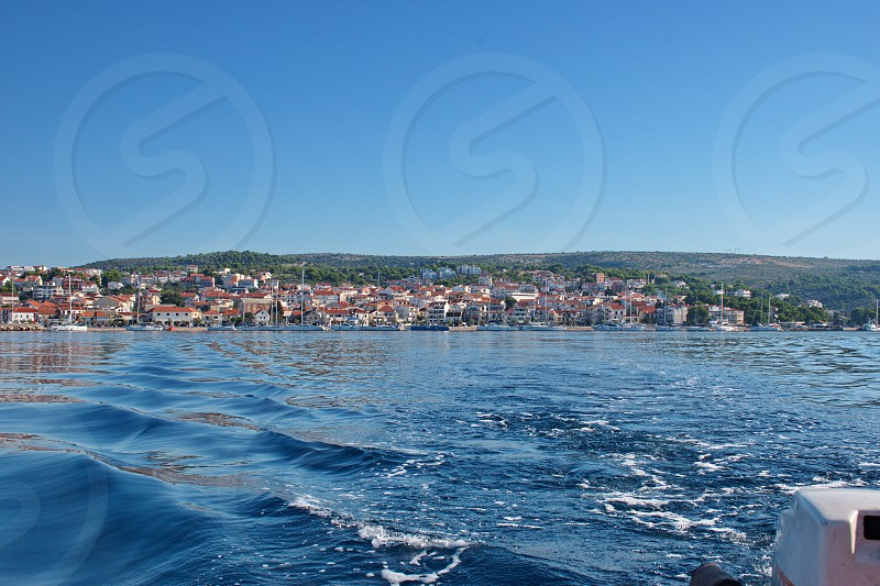 Sailing on motor boat on Adriatic sea with Primosten cityscape in the background. Vacation in Croatia photo