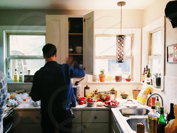 man wearing blue long sleeve shirt and white wooden overhead kitchen cabinet photo