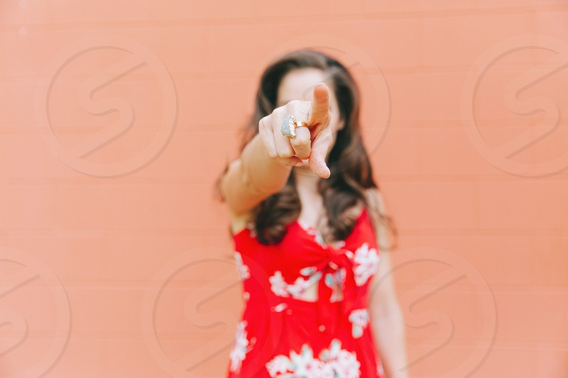 A young woman pointing against an orange wall.  photo