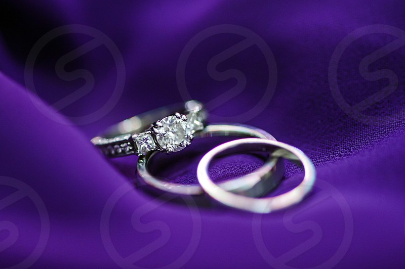 silver wedding rings on purple fabric photo