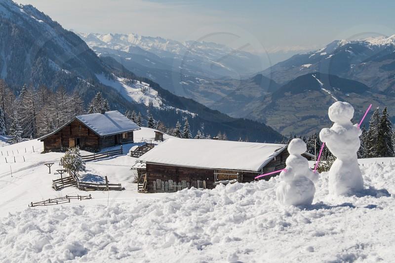 white snowman near brown house photo