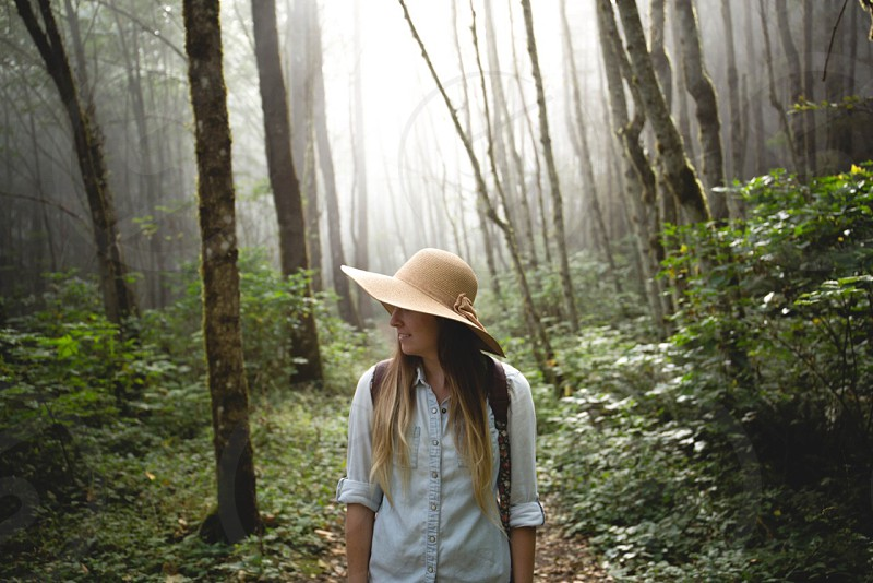woman in white button up shirt and beige summer hat walking under the green trees photo