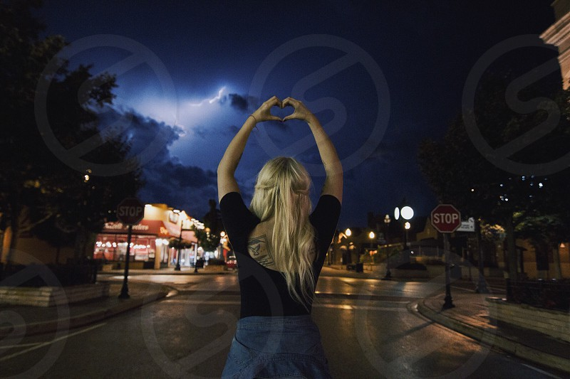 woman in black quarter strap back less top wearing blue denim skirt making heart sign during night time with lightning storm photo