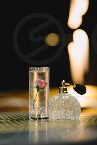 clear glass container with pink rose flower inside beside clear glass perfume bottle photo