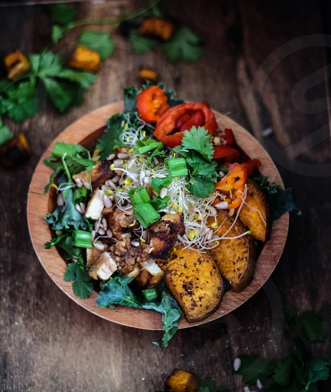 A flavourful bowl of teriyaki tofu sweet and spicy roasted sweet potatoes banana peppers kale sprouts and pine nuts all drizzled with a ginger-tahini dressing. Nutritious delicious and vegan. photo