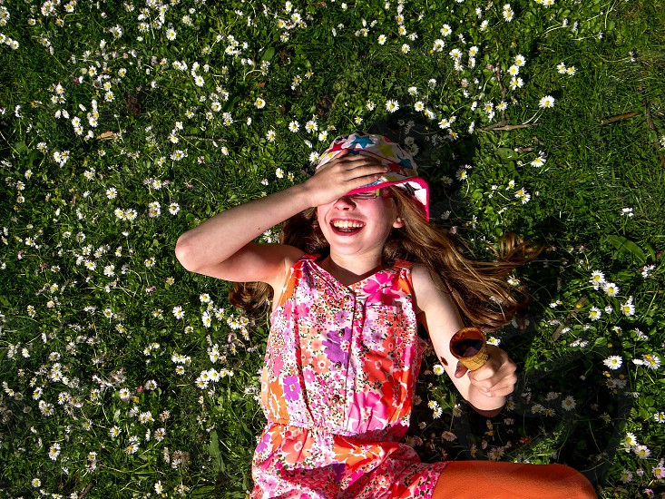 girl in multicolored floral printed dress lying on grass smiling photo