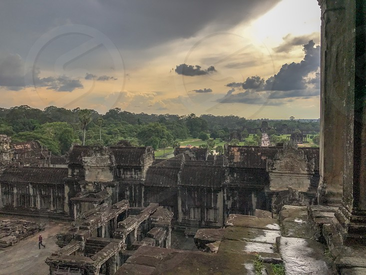 Outdoor day colour landscape horizontal Angkor Wat Temple complex Cambodia Asia Asian east eastern orient spiritual holy religious religion Buddhism Buddhist ancient crumbling stone carved stonework masonry elaborate intricate columns travel traveller travelling tourism tourist wanderlust adventure explore exploration cloud cloudy clouds atmospheric sunset birds flight rain rainy drops droplets raining view vista scenic vivid wet photo