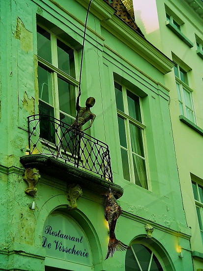 view of a green building with a fisherman and a fish statue photo