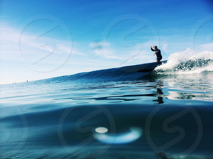 person wearing black surfing blue wave photo