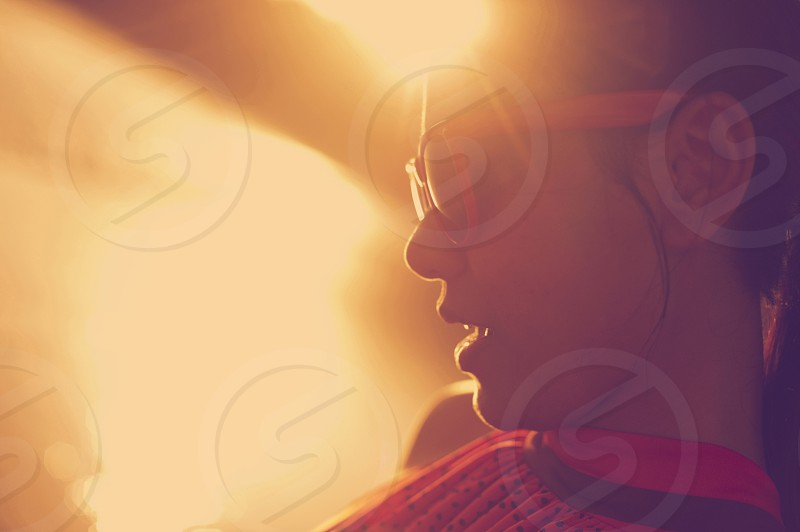 Profile of a young Asian woman in early morning sunlight at the beach wearing sunglasses photo