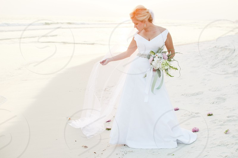 woman in white wedding dress holding a bouquet photo