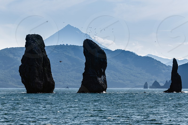Beautiful seascape Kamchatka: view on Three Brothers Rocks - natural monument of Kamchatka in Avacha Bay (Avachinskaya Bay) on background Vilyuchinsky Volcano. Russia Far East Kamchatka Peninsula. photo