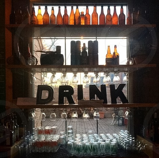 """""""Drink"""" Bar Scene With Amber Bottles & Glassware and Window  photo"""