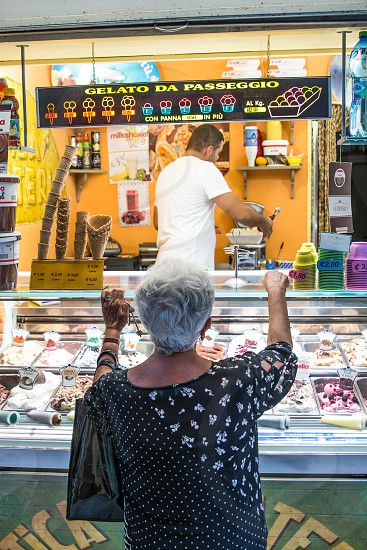 woman in white and black floral polka dot top holding ice cream display counter of gelato da passeggio store with man in white t shirt serving her photo