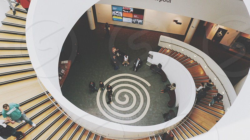 white and brown spiral staircase with group of people photo