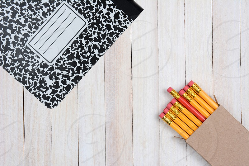 High angle shot of a box of pencils and a composition book on a white wood surface. Objects are in opposite corners of the frame. photo