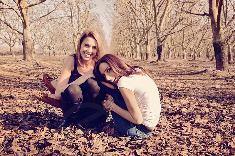 2 woman sitting on dirt road photo