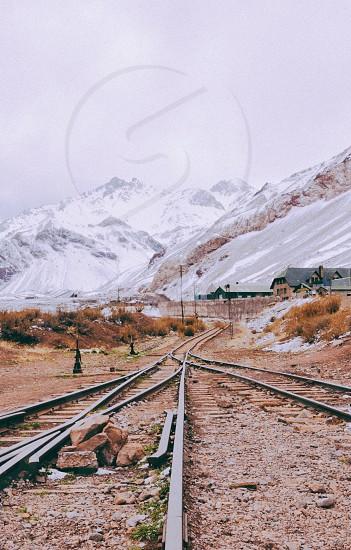brown rocks between metal train tracks photo