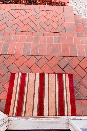 red white and brown stripe patio rug on red brick tiles photo