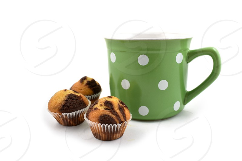 Green mug with dots. Muffins and green mug. Chocolate muffin with cup on a white background. Big spotted mug  photo