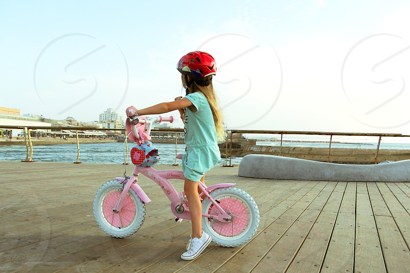Little blond caucasian girl riding on pink bicycle on the jetty by the sea and look at the horizon. She wears a red helmet on her head. photo