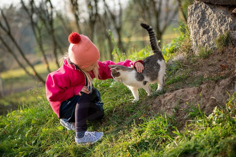 Little girl hugging cat outside photo