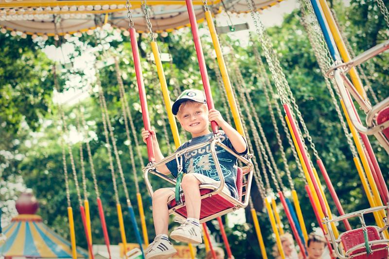 boy youth child amusement park ride fun summer fair yellow swings giant swings around circle carousel green blue hat cap happy rides blonde teeth smile carnival festival photo