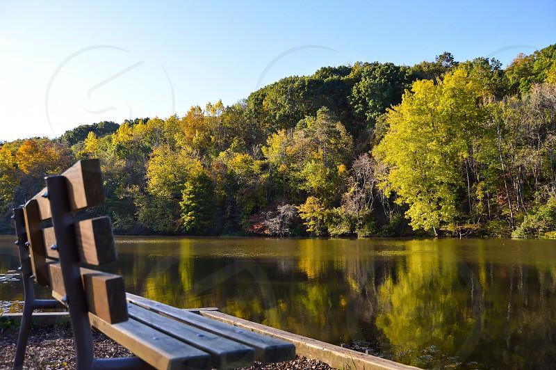 Park bench lake fall leaves. photo