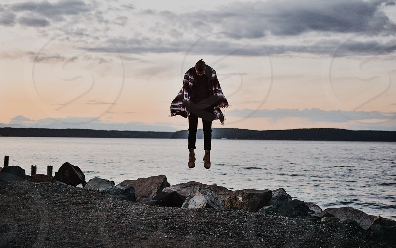 man in red and white scarf near body of water during daytime photo