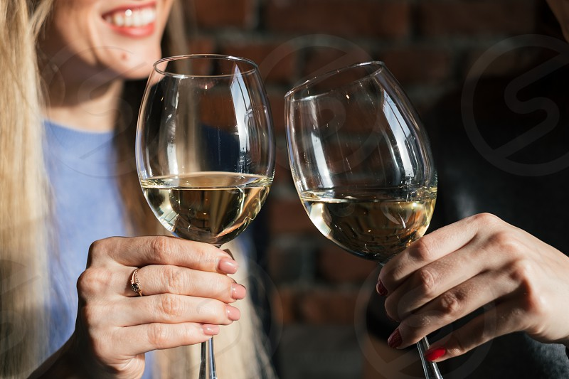 Two woman holding glass of white wine photo